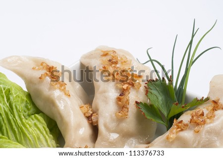 Dumplings with fried onion and herbs served an a plate.