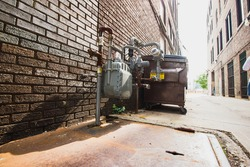 Dumpster sitting in an alley next to a gas meter and brick buildings surrounding