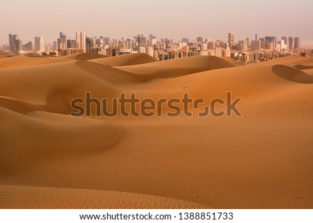 Dunes of Desert at dawn and skyscrapers of  Dubai (United Arab Emirates)