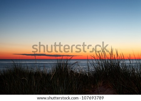 Dunes with grass silhouetted by a summer sunset over Lake Michigan.