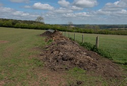 Dung or Muck Heap on the Edge of a Field on a Farm with a Panoramic Rural View and a Cloudy Blue Sky in the Devon Countryside, England, UK