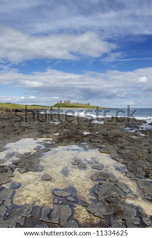Dunstanburgh Castle from the coastal path to Craster with rockpool in the foreground