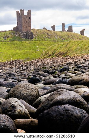 Dunstanburgh Castle seen from rocky beach