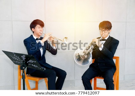 duo musician : Portrait young Asian men playing music : Two Asian play triple and trumpet and French trumpet. Horn in the show