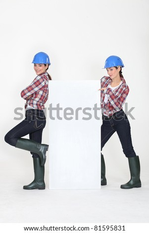 duo of young women with hard hat and white canvas