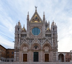Duomo di Siena at sunrise, a black and white marble church typical of medieval gothic architecture, in the famous town of Siena, Tuscany, Italy