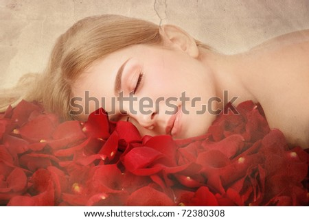 Duotone colored shot of young beautiful woman sleeping in red rose petals on vintage damaged grainy background