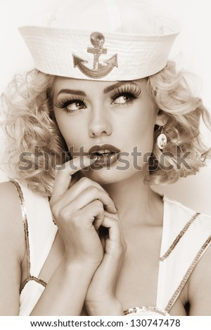 Duotone portrait of young beautiful sexy girl with blond curly hair and stylish make-up dressed as sailor
