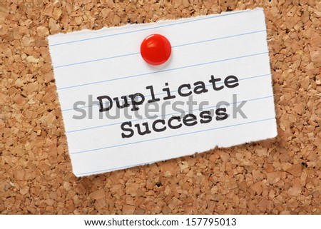 Duplicate Success typed onto a scrap of lined paper and pinned to a cork notice board. In business we search for best practices that produce the results we want and then try to build on the success.