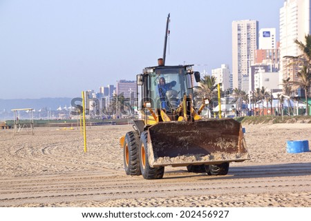 DURBAN, SOUTH AFRICA - JULY 2, 2014; Payloader works on beach on Golden Mile beachfront in Durban, South Africa