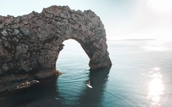 Durdle Door arch with paddle boarder in the ocean.