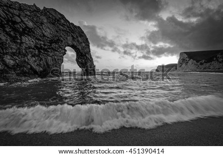 Durdle Door on the Jurassic coast of Dorset with crashing wave in Black and White
