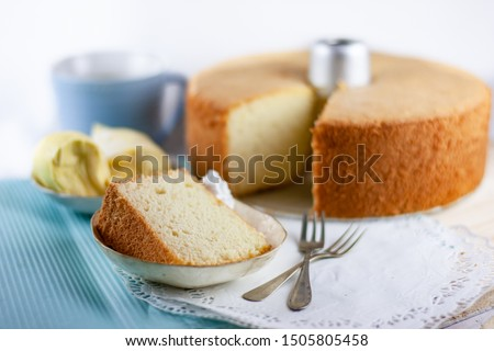 Durian Chiffon Cake, a typical asian cake variation, served in a slice with the whole cake in the background in chiffon cake tin