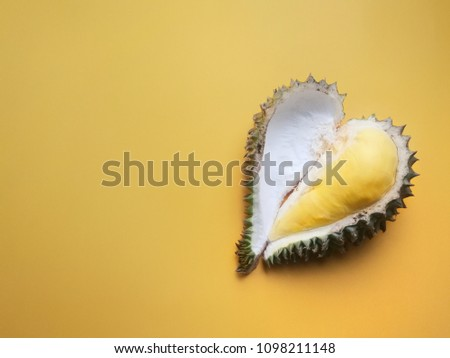 Durian is a famous fruit of Thailand placed on right side yellow background with heart shape minimal style.copy space.