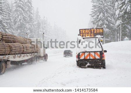 During a snow storm, a loaded log truck passes a highway department pickup tuuck with an illuminated chains required sign mounted on it, santiam pass, Oregon #1414173584
