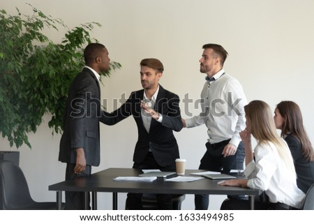 During group meeting African and Caucasian business partners having conflict fighting, colleague stop a scuffle, multiracial people express aggression negative attitude, racial discrimination concept Photo stock ©