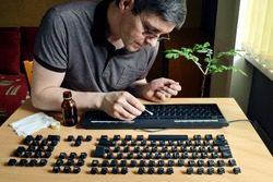 During isolation, a person is busy cleaning the dirty surface of a computer keyboard. He disassembled it to thoroughly clean the inaccessible parts