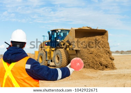 During leveling construction site young signalman, spotter gives visible signals with radio to heavy equipment, forklift and grader. Perfect background of construction operations. #1042922671