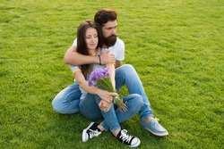 During outdoor recreational activities. Couple in love sit on green grass outdoor. Summer vacation. Enjoying fresh outdoor air. Rest and relaxation. Healthy outdoor recreation. Summertime.