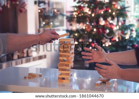 Photo of  During the Christmas season, the family plays board games together. Woman and man build a wobbly tower from wooden blocks. In the background is the Christmas tree.