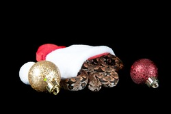 Durmeril's Boa Snake slithering out of Santa Hat surrounded by holiday Christmas ornaments, isolated on black with copy space.