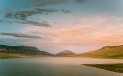 Dusk falls over reservoir with view of foothills of Rocky mountains on horizon on a beautiful and calm evening near Cody, Wyoming, USA.