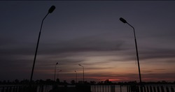 Dusk over a river with lamp posts in a silhuette