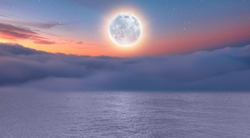 Dusk sky with full moon in the clouds at subset, calm sea in the foreground