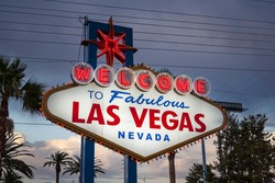 Dusk view of the famous Welcome to Fabulous Las Vegas sign with palm trees and overhead wire grid in background.