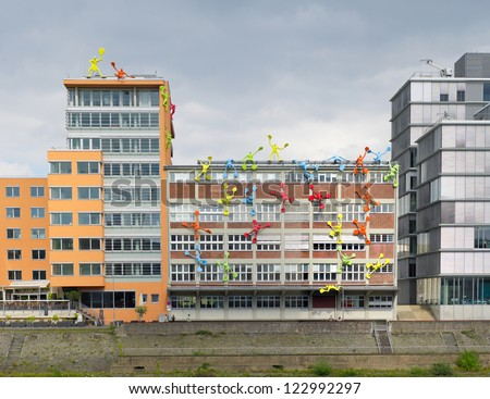 DUSSELDORF - AUGUST 11: Media Harbor on august 11, 2012 in Dusseldorf. This office building is emphasized by 28 giant plastic figures, known locally as Flossies, 'climbing' the dockside of the office