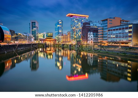 Dusseldorf, Germany. Cityscape image of Düsseldorf, Germany with the Media Harbour and reflection of the city in the Rhine river, during twilight blue hour.