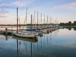 Dusseldorf, Germany - Peaceful evening at Lake Unterbacher See. Moored sailboats in the marina. Beautiful landscape before the sun goes down.