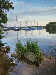 Dusseldorf, Germany - Peaceful evening at Lake Unterbacher See. Moored sailboats in the marina. Beautiful landscape before the sunset.