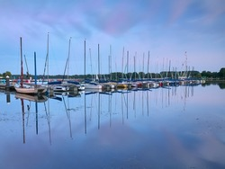 Dusseldorf, Germany - Peaceful evening at Lake Unterbacher See. Moored sailboats in the marina. Beautiful landscape after the sunset.