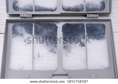 Dust and dirt trapped by the clothes dryer filter. clothes dryer lint filter that is covered with lint. Taking the lint out from dirty air filter of the dryer machine Stockfoto ©