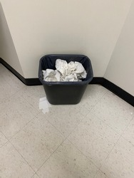 Dust Bin full of used toilet papers in washroom on the floor. Dust bin with tissue papers in washroom