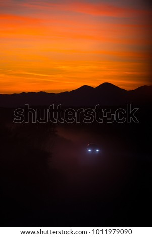 Dust settles in the Arizona wilderness at dusk as a loan vehicle travels to an unknown destination.Dust settles in the Arizona wilderness at dusk as a loan vehicle travels to an unknown destination. #1011979090