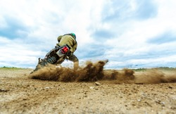 Dust splash from enduro motocycle race. Motocross bike in a race representing concept of speed and power in extreme man sport