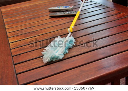 dusting a wooden coffee table with a synthetic duster, closeup perspective shot - stock photo