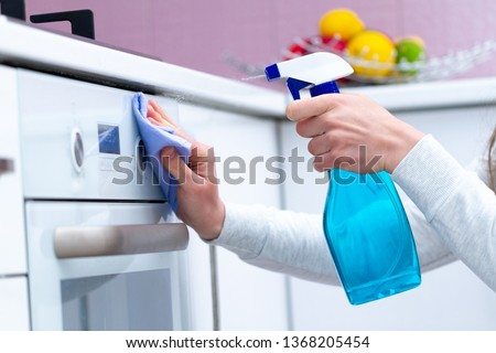 Dusting and polish gas stove using cleaning products in kitchen at home. Housekeeping, household chores. Clean house, cleanliness