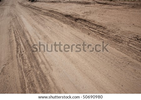 Dusty and rutted dirt road. Focus on tire ruts.