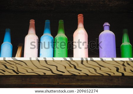Dusty colored bottles on a white and black striped wooden shelf.