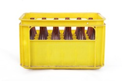 Dusty vintage yellow beer crate with empty brown beer bottles on white background