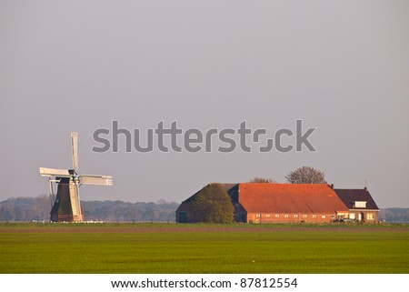 dutch agricultural landscape with farm and windmill