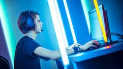 Dutch Angle of a Young Pro Gamer Playing in Online Video Game, talks with Team Players through Microphone. Neon Colored Room. e-Sport Cyber Games Internet Championship.