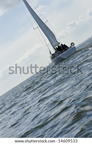 Dutch angle shot of a fully crewed yacht out at sea