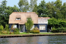 Dutch blue wooden house in traditional style, typical straw roof and charming garden terrace along water in scenic village Giethoorn, 'little Venice', Netherlands