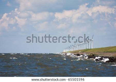 Dutch breakwater with windmills during a heavy storm