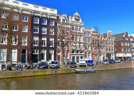 Dutch buildings along sunny canal in Amsterdam, Holland  #411865084