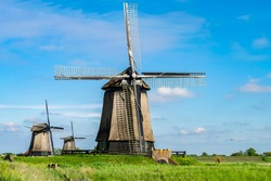 Dutch countryside traditional landscape with wooden windmills. Historical and architectural attractions in the Netherlands. Travel and vacation in the Netherlands.